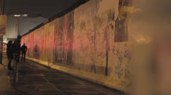 People walking next to Berlin wall at night Stock Footage