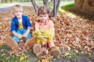 Cute kids sitting on ground in park Stock Photos