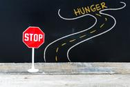 Mini STOP sign on the road to HUNGER Stock Photos