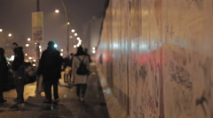 People walking next to Berlin wall at night, car lights casting shadows Stock Footage