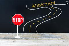 Mini STOP sign on the road to ADDICTION Stock Photos