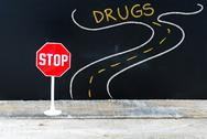 Mini STOP sign on the road to DRUGS Stock Photos