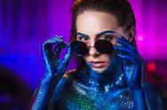 Portrait of beautiful woman painted with cosmic colors and spangled. Stock Photos