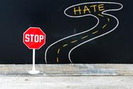 Mini STOP sign on the road to HATE Stock Photos