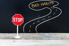Mini STOP sign on the road to BAD HABITS Stock Photos