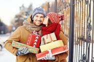 Happy girl with giftboxes kissing her boyfriend outdoors Stock Photos