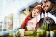 Young couple with hot drinks looking through window in cafe Stock Photos