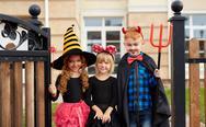 Little kids in Halloween attire looking at camera Stock Photos