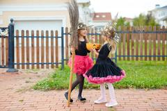 Halloween girl sharing treats with her friend Stock Photos