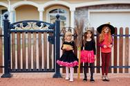 Three girls standing by gate with Halloween treats Stock Photos