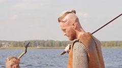 Mad vikings on the Drakkar on the river shore Stock Footage