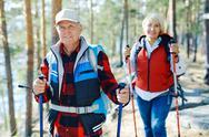 Modern senior couple trekking in natural environment Stock Photos