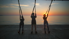 Silhouettes of sportive people training arms with trx at sunrise. Slow motion. Stock Footage