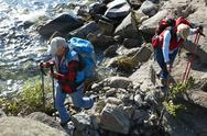 Active senior people with trekking sticks going by river Stock Photos