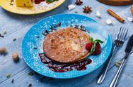 Restaurant dessert. Pancakes with raspberry sauce on blue wood Stock Photos
