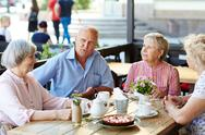 Senior friends having tea with dessert in cafe Stock Photos
