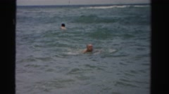 1955: old guy wearing yellow trunks happily swims through the waves of the ocean Stock Footage