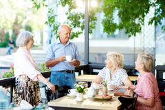 Mature people with cups of tea relaxing in cafe Stock Photos