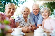 Grey-haired senior females and man sitting in outdoor cafe Stock Photos
