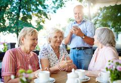 Happy aged women talking by table with senior man with cellphone standing near b Stock Photos