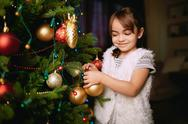 Pretty girl decorating Christmas treee with toy bubbles Stock Photos