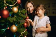 Pretty girl and her mother looking at one of decorative xmas bubbles on firtree Stock Photos
