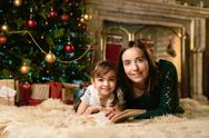 Happy young female and her daughter lying on the floor by Christmas tree Stock Photos