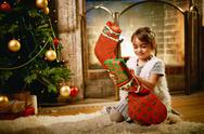 Little girl putting xmas surprise into gift sock Stock Photos