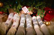 Human feet in woolen socks by xmas tree Stock Photos