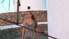 Blonde model leans against windmill sunset mykonos greece Stock Footage