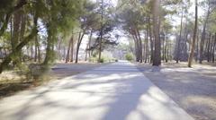 Walking on concrete path towards settlement through woods 4K Stock Footage