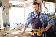Contemporary carpenter with tool-belt looking at camera in workshop Stock Photos