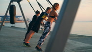 Beautiful sportive people training arms with trx at sea sunrise. Slow motion. Stock Footage