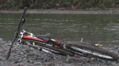 A mountain biker picking bike off rocky ground with a river in the background. Stock Footage