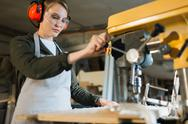 Young woodworker processing timber on special machine Stock Photos
