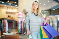 Blond girl with paperbags shoppingg in trade center Stock Photos