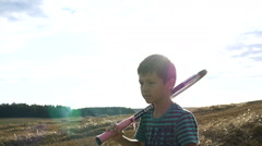 Boy goes on a field with a tennis racket, tennis player boy in the field Stock Footage