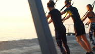 Beautiful sportive people training with trx at seaside at sunrise. Slow motion. Stock Footage