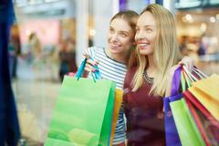 Happy shopper pointing at something in shop-window Stock Photos