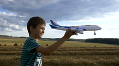 Boy dreams of becoming a pilot in the field, boy playing with plane Stock Footage
