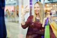 Smiling shopper posing for selfie in trade center Stock Photos