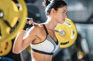 Sportive female with weight working out in gym Stock Photos