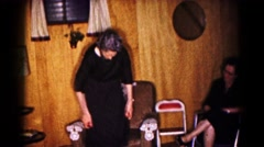 1961: group of men and women in dark clothes, woman straightens her dress Stock Footage