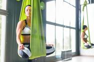 Young woman relaxing in hammock in pose of lotus in gym Stock Photos