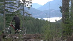 A mountain biker lifting bike over his head in celebration. Stock Footage
