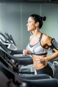 Young sporty woman running on treadmill in gym Stock Photos