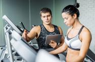 Young trainer explaining how to regulate speed of treadmill to active girl Stock Photos