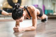 Female athlete doing planks on the floor Stock Photos