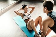 Female in activewear doing sit-ups while trainer helping her Stock Photos