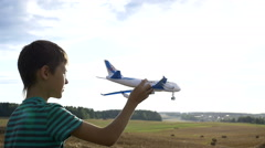 Boy playing with plane, boy dreams of becoming a pilot in the field Stock Footage